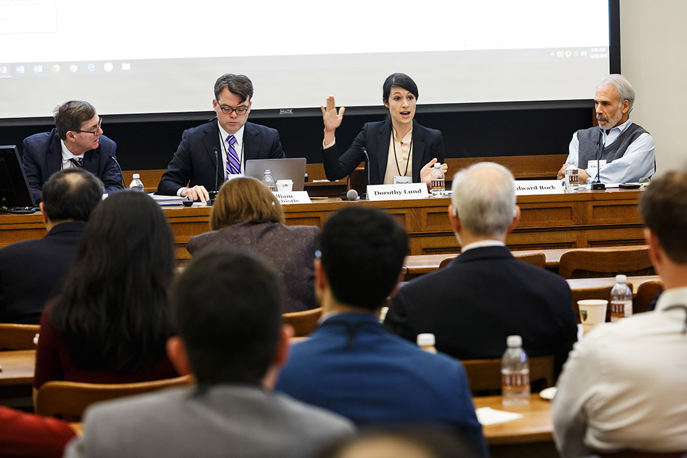 USC Law Prof. Dorothy Lund presenting, while Harvard Law Prof. Lucian Bebchuk, Chicago-Kent College of Law Prof. William Birdthistle, and NYU Law Prof. Edward Rock listen