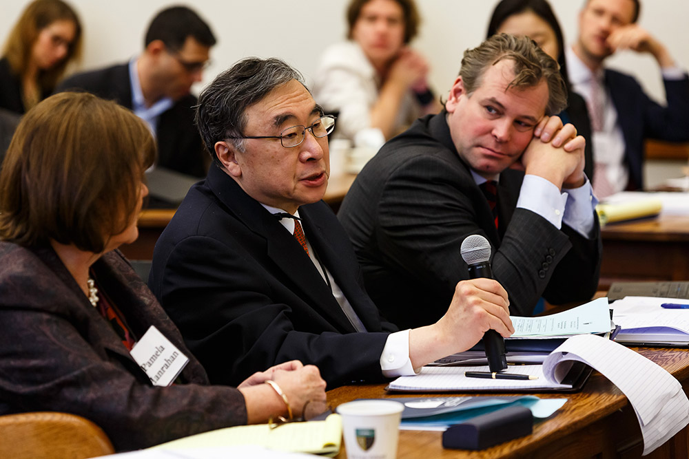 Texas Law Prof. Henry T.C. Hu '79 asking a question, while U. of New South Wales Bus. Prof. Pamela Hanrahan and U. of Luxembourg Law Prof. Dirk Zetzsche listen