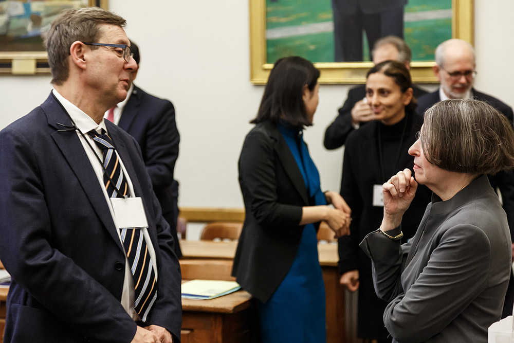 Harvard Law Prof. Lucian Bebchuk and YLS Prof. and Center Dir. Roberta Romano '80 conversing (foreground), while Center Exec. Dir. Nancy Liao '05 welcomes SEC Div. of Investment Mgmt. Dir. Dalia Blass (background)
