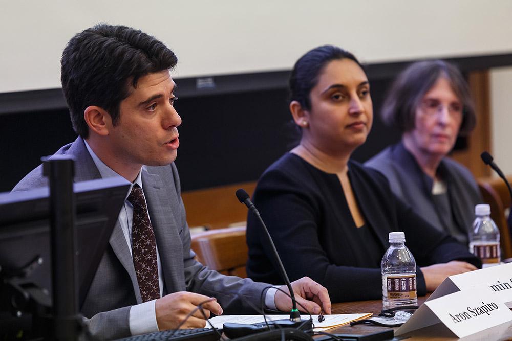 Aron Szapiro presenting, while Jasmin Sethi and YLS Prof. and Center Dir. Roberta Romano '80 listen