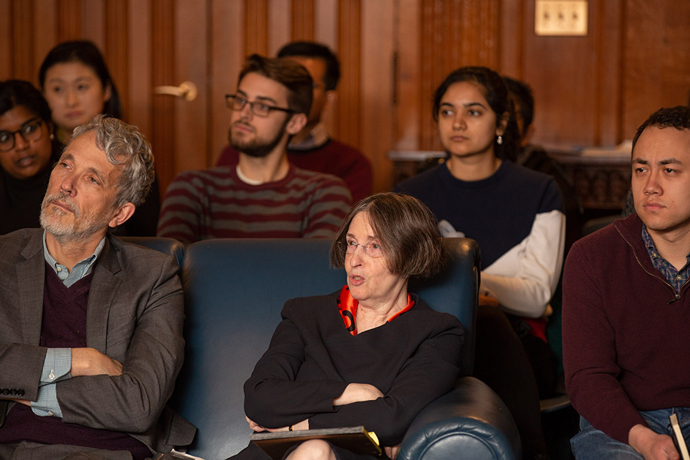 YLS Prof. and Center Dir. Roberta Romano '80 (center) asking Vice Chair Randal K. Quarles '84 a question, while YLS Prof. Ian Ayres '86 (left) and audience members listen
